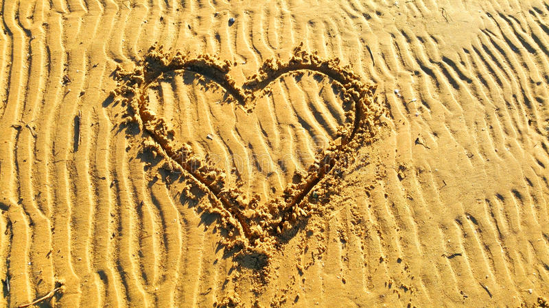 Drawing heart on the sand. For Valentin day royalty free stock photos