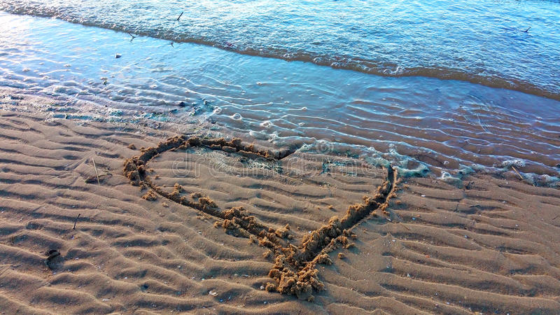 Drawing heart on the sand. For Valentin day royalty free stock photo