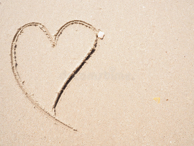 Drawing heart shape on the beach. In the low tide stock image