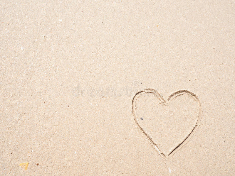 Drawing heart shape on the beach. In the low tide stock photos