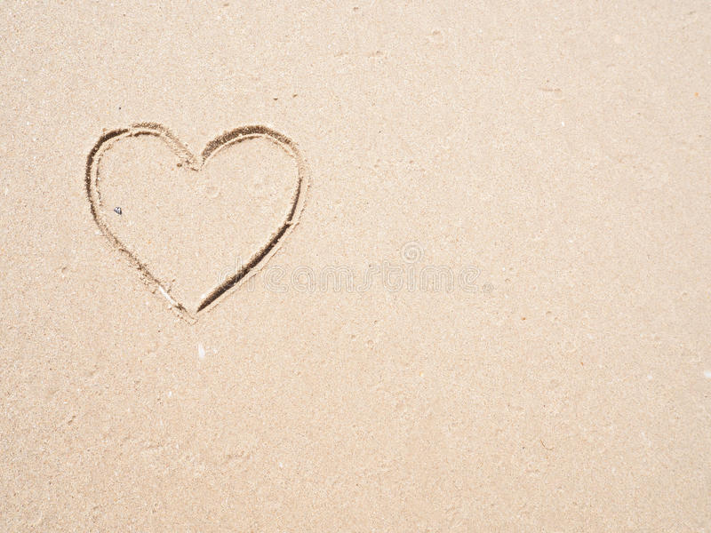 Drawing heart shape on the beach. In the low tide stock images
