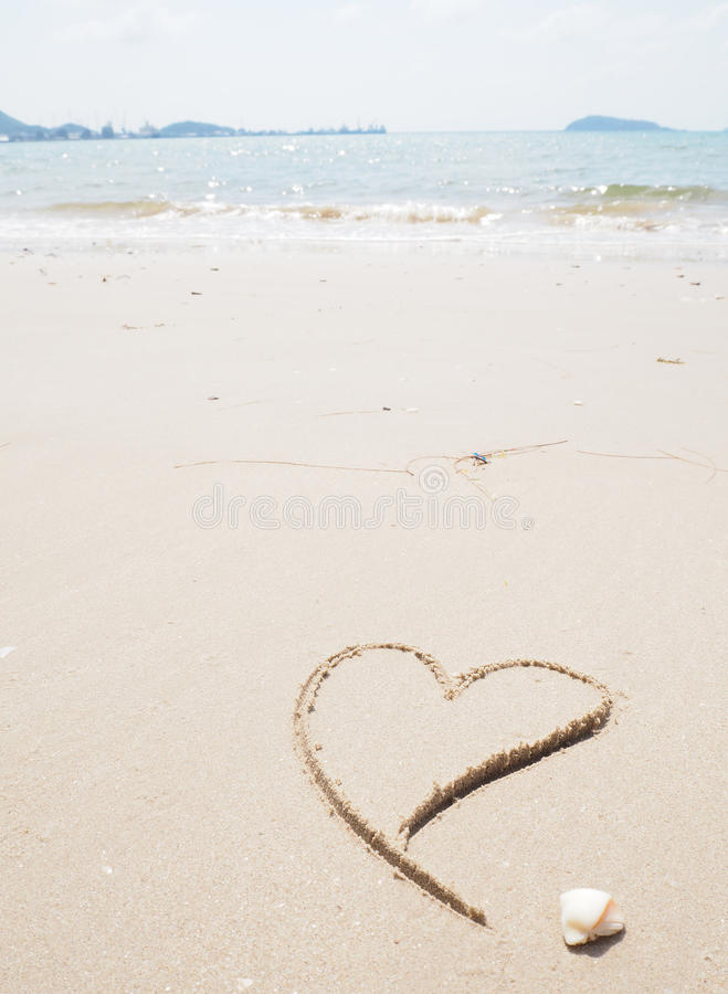 Drawing heart shape on the beach. In the low tide royalty free stock image