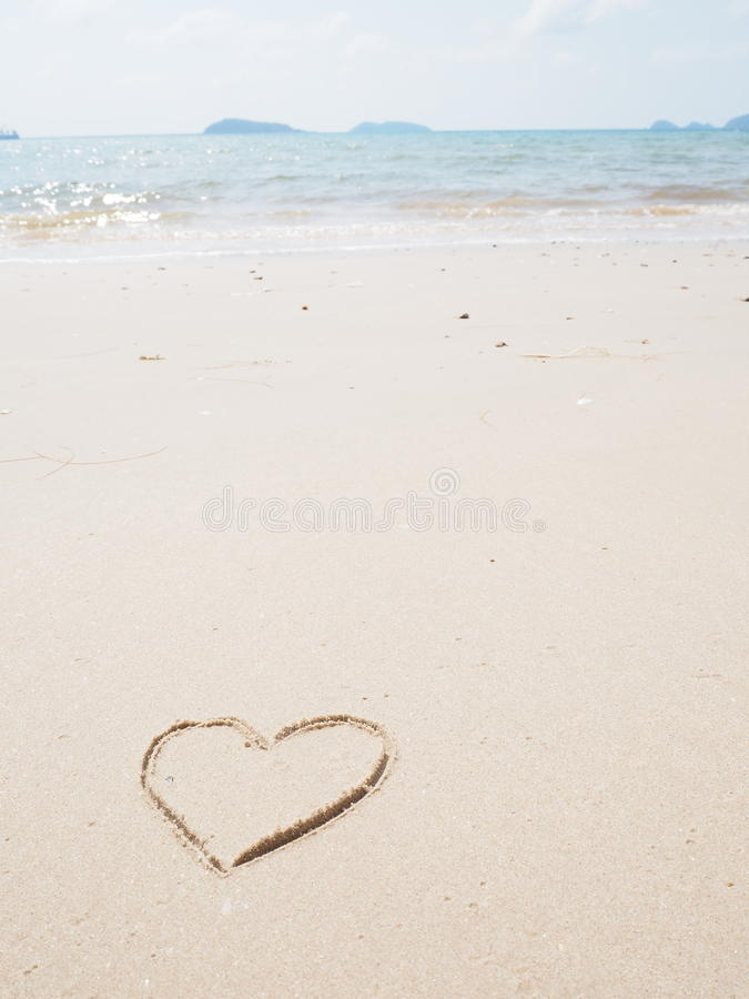 Drawing heart shape on the beach. In the low tide stock photography