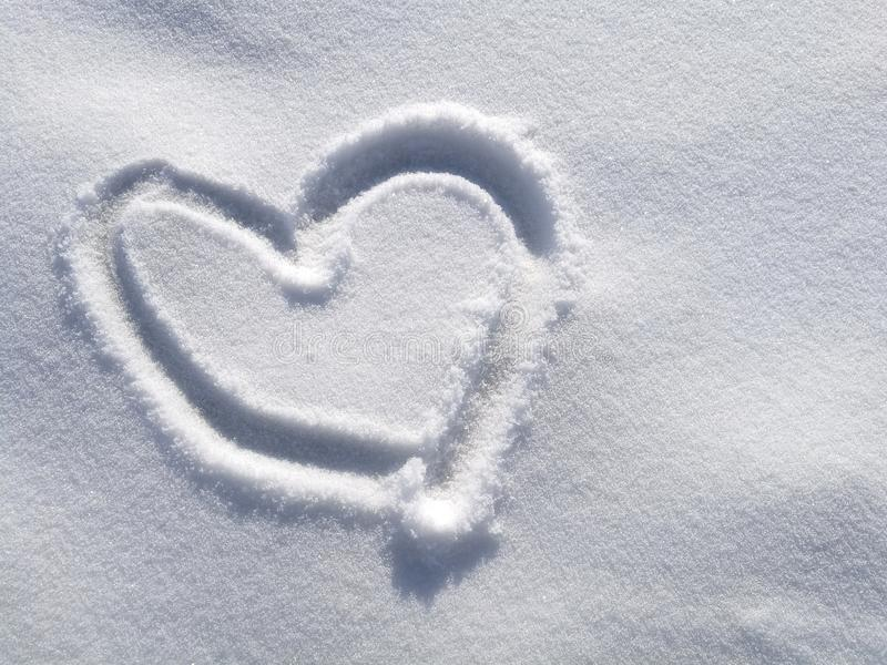 Drawing heart on snow in the winter time background, valentine, symbol. Drawing heart on snow in the winter time background, valentine, valentine symbol royalty free stock photos