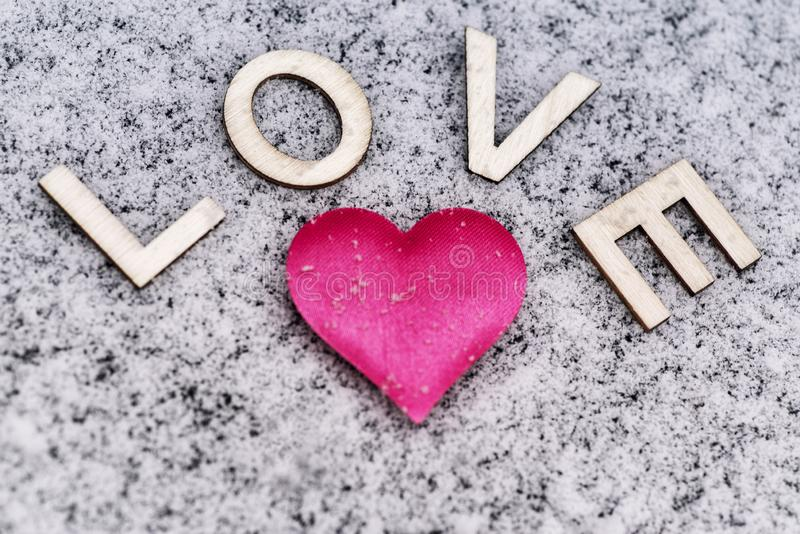Drawing of a heart on the snowy .Valentine`s Day. Heart of pink in the snow with the letters sweet. Valentine`s Day. Soft focus. royalty free stock images