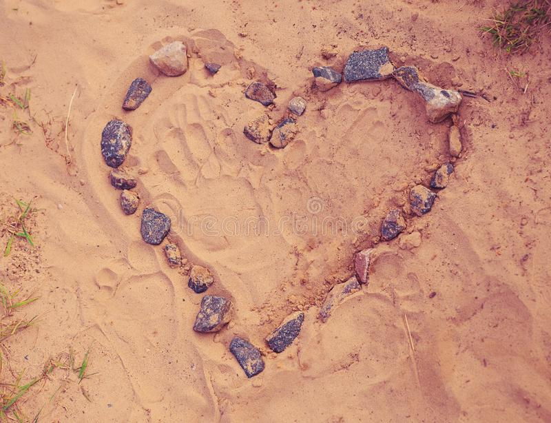 Drawing Heart of stones laid on warm sand. Toned, soft focused. Drawing Heart of stones laid on warm sand at the beach. Toned, soft focused royalty free stock photo