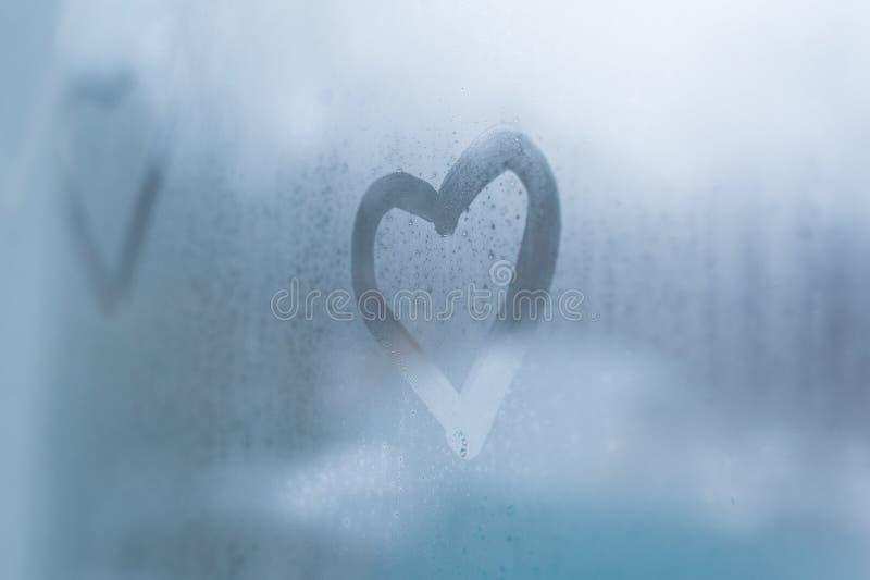 Drawing a heart on sweaty glass on window stock photography