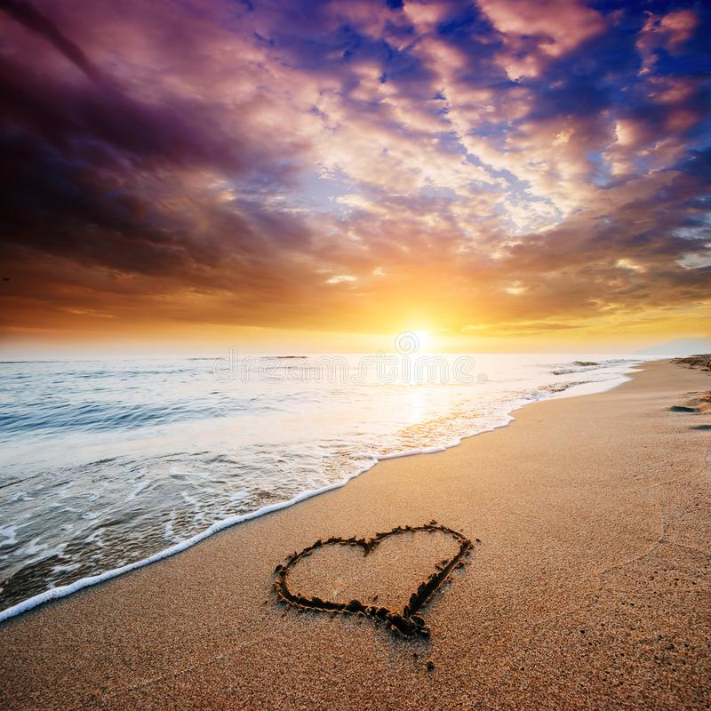 Drawing heart on yellow sand on the fantastic sunset royalty free stock photos
