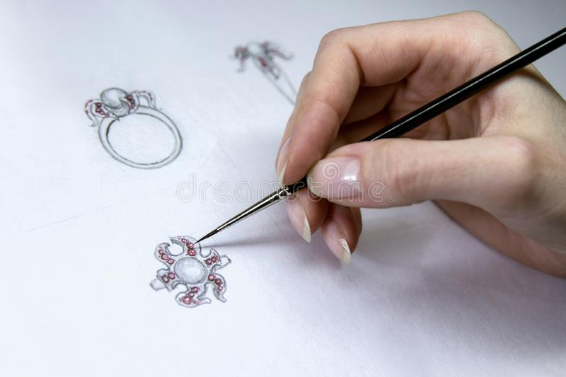 Drawing Jewelry Design. Artist designer drawing sketch jewelry on paper . Hand made. stock image