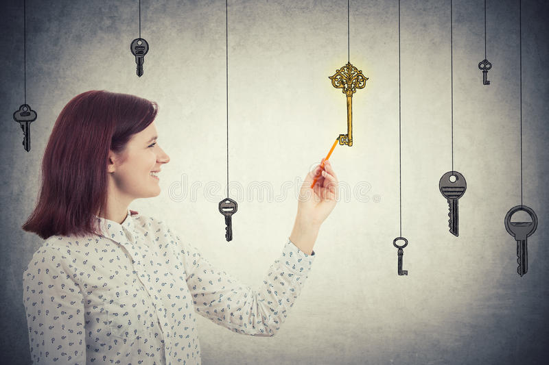 Drawing the key to success. Smiling young businesswoman drawing a vintage golden key to success among others made of steel hanging. Concept of business stock images
