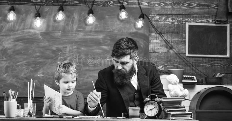 Drawing lesson concept. Teacher with beard, father and little son in classroom while drawing, creating, chalkboard on. Background. Child and teacher on busy royalty free stock photo