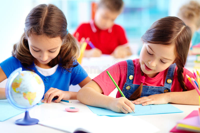 Drawing lesson. Portrait of lovely girls drawing at workplace with schoolboys on background royalty free stock photography