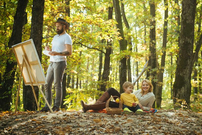 Drawing from life. Painter artist with family relaxing in forest. Painting in nature. Start new picture. Capture moment. Beauty of nature. Bearded men women stock photography