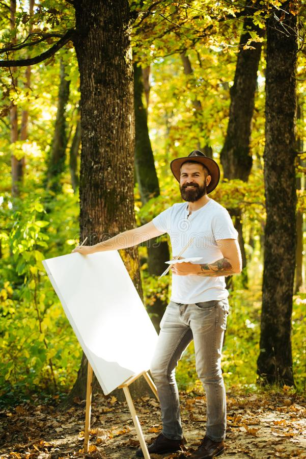 Drawing from life. Painter artist forest. Art concept. Painting in nature. Start new picture. Painter with easel and. Canvas. Capture moment. Bearded man stock images