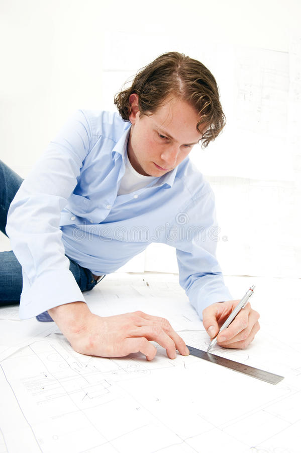 Drawing a line. Engineer drawing a line on a set of technical drawings using a pencil and a ruler stock photo