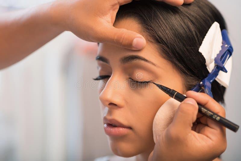 Drawing liner. Close-up image of make-up artist using pen eyeliner stock images