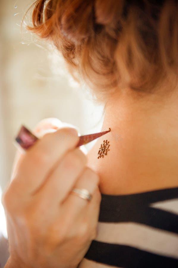Drawing mehndi on the girls neck stock photo