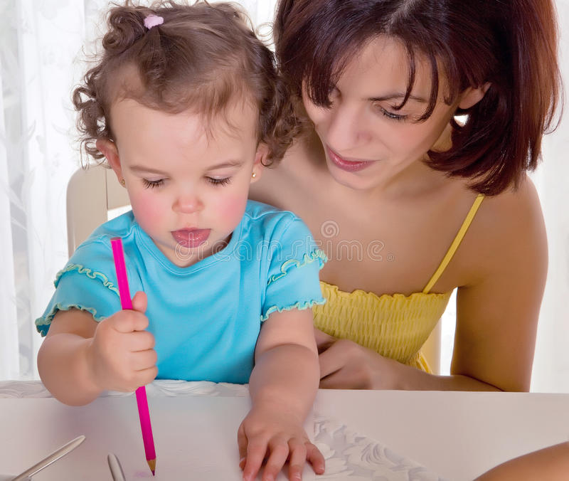 Drawing for mommy. Little toddler girl making a drawing for her mother stock photo