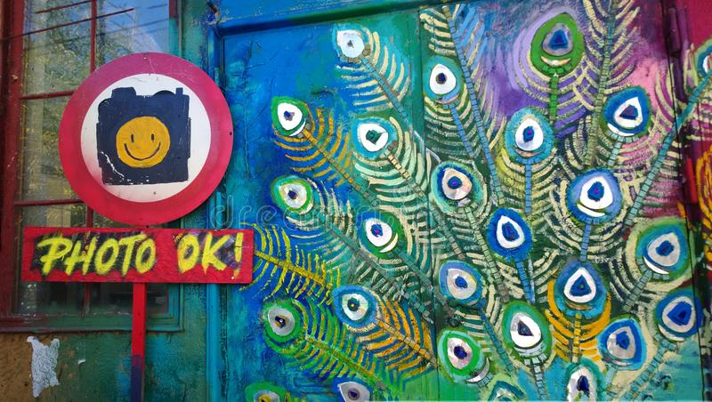 Drawing on one of the buildings in the free city of Christiania with the sign permission to take a photo. A bright wall at the ent royalty free stock image