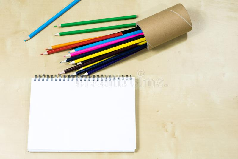Drawing pencils and a sketching notebook on a wooden table. Sketchpad on the drawing board. stock images