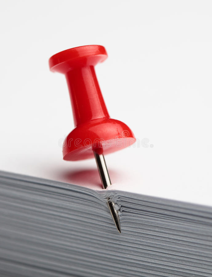 Drawing pin in paper pile. Macro of pin on blank paper stack stock photography
