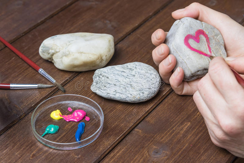 Drawing the red heart frame on stone. Female hand is drawing the red heart frame on a stone by brush royalty free stock photography