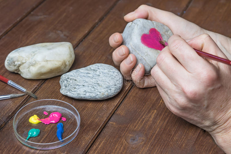 Drawing the red heart on stone. Female hand is drawing the red heart on a stone by brush stock photo