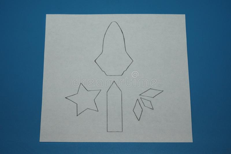 Drawing of a rocket and stars on a white sheet of paper drawn in pencil.  royalty free stock images