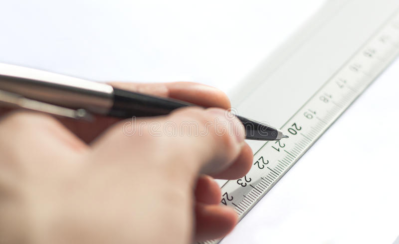 Drawing by a ruler with hand. A hand holding a pencil ready to draw from the ruler stock photos
