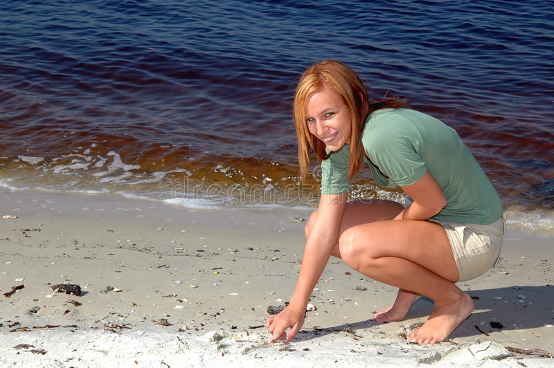 Drawing in the sand. A cute teen drawing in the sand royalty free stock photos