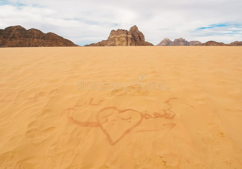 The drawing in the sand in the desert. Broken heart royalty free stock image