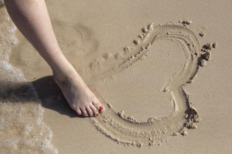 Drawing in the sand. Drawing a heart in the sand with a woman`s foot stock photography