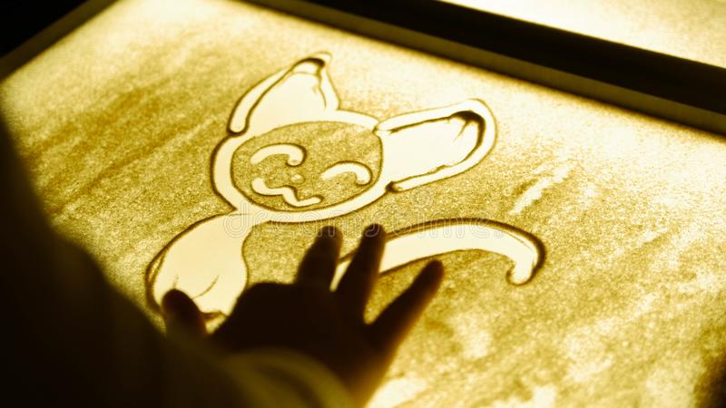 Drawing with a sand on the screen. Drawing a cat. Darkness royalty free stock photography