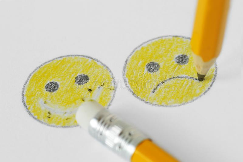 Drawing of smiley face with negative and positive expression with pencil and rubber - Negative emotion concept stock photography