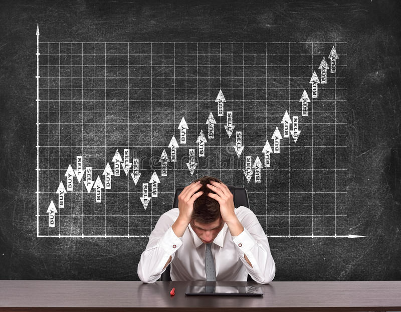 Drawing stock chart on blackboard. Tired businessman sitting at table and drawing stock chart on blackboard royalty free stock image