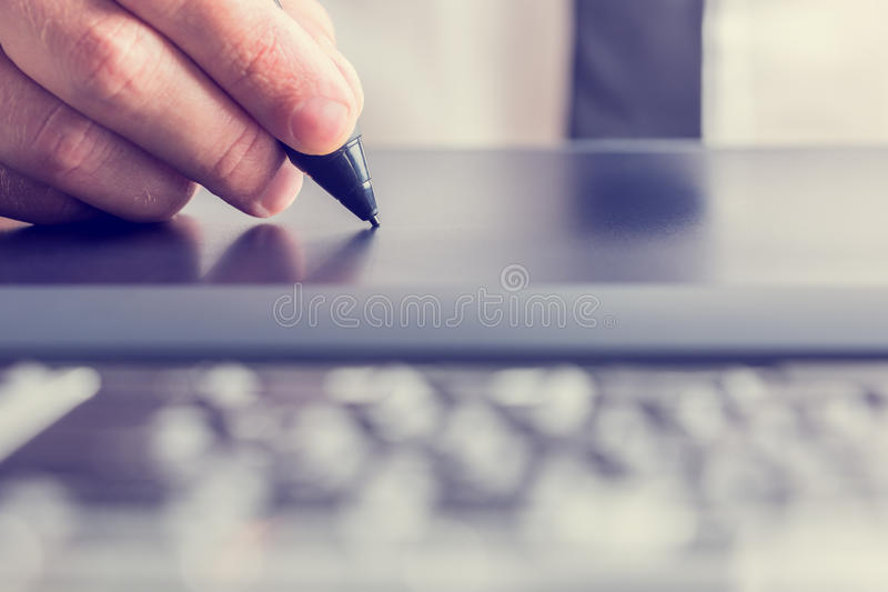 Drawing with the stylus on a grey graphics tablet. Retro image of male hand of a designer drawing with the stylus on a grey graphics tablet, close-up stock photo