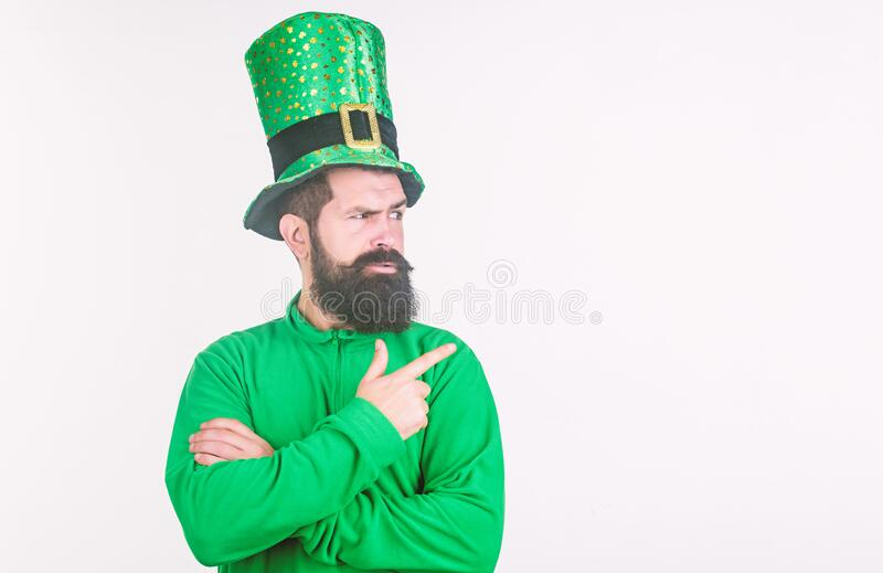Drawing your attention. Hipster wearing leprechaun hat and costume pointing finger. Bearded man celebrating saint stock photo