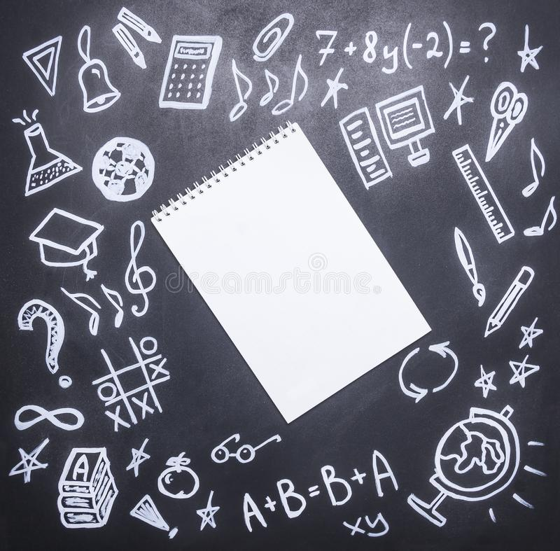 Drawings on the chalkboard on the new academic year, fall, school supplies, drawn around a notebook with pencil, place for text, stock photo