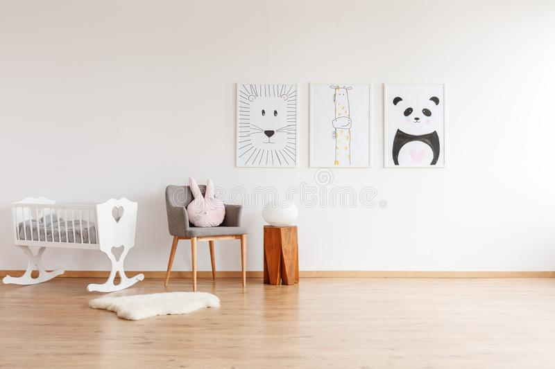 Drawings in baby`s room. Drawings on white wall above grey chair with pillow and wooden stool in baby`s room with white crib and rug stock image