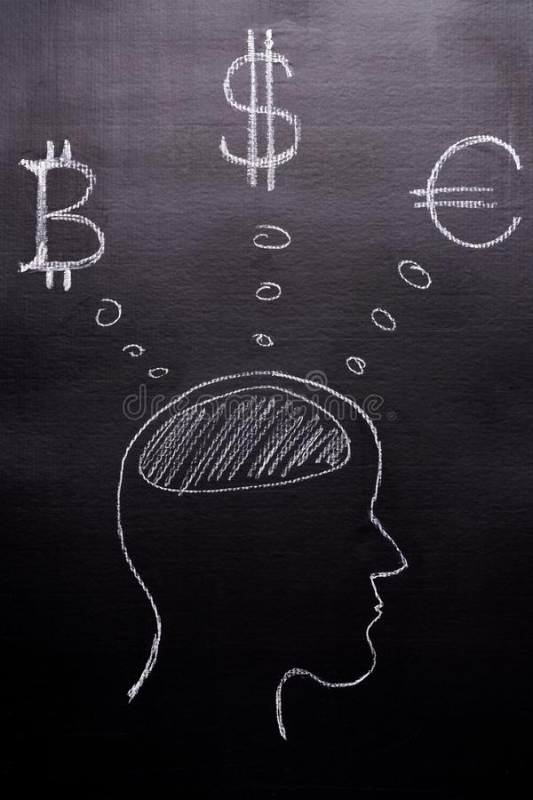 Drawn with chalk on a black background - the man`s head with thoughts of world currencies, Bitcoin, Dollar, Euro. The concept of royalty free stock photo