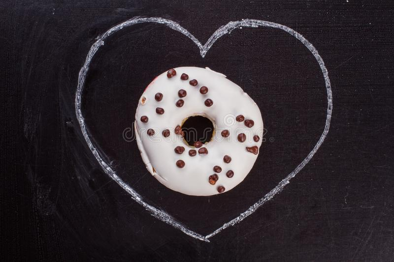 Drawn heart and donut on black background. Hand drawn chalk heart and white glazed donut. Sweets for Valentines Day stock images