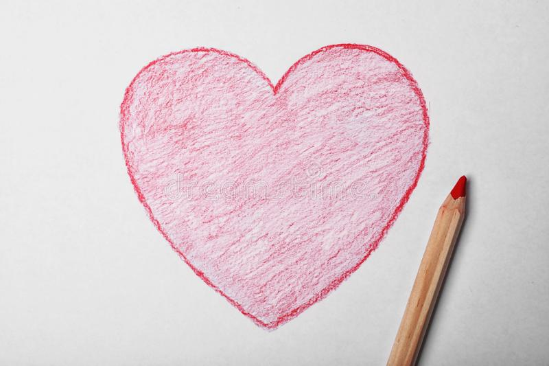 Drawn heart and pencil on sheet of paper. Top view stock image