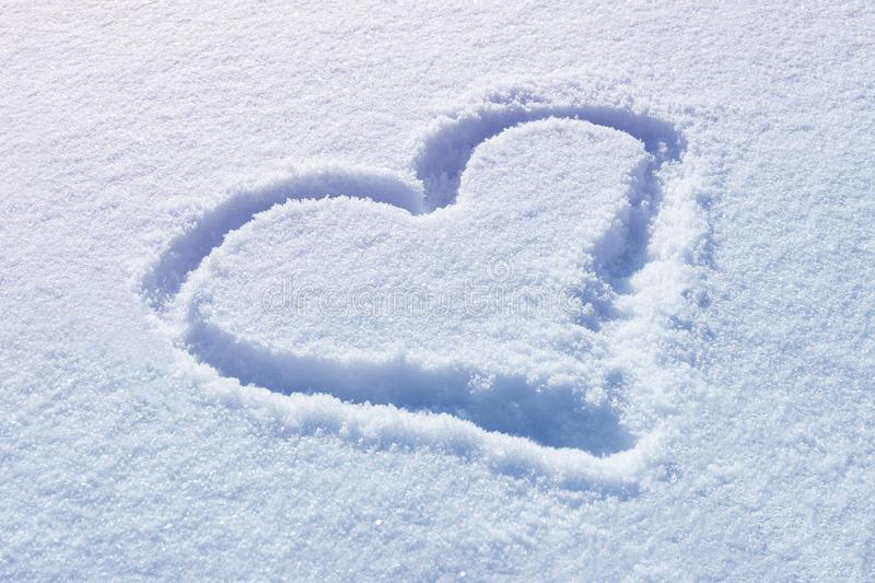 Drawn heart shape on snow. Background royalty free stock photography