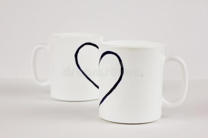 Drawn heart and two cups on white background. Valentine`s day, love, couple, wedding concept. Drawn heart and two white cups on white background. Valentine`s day royalty free stock image