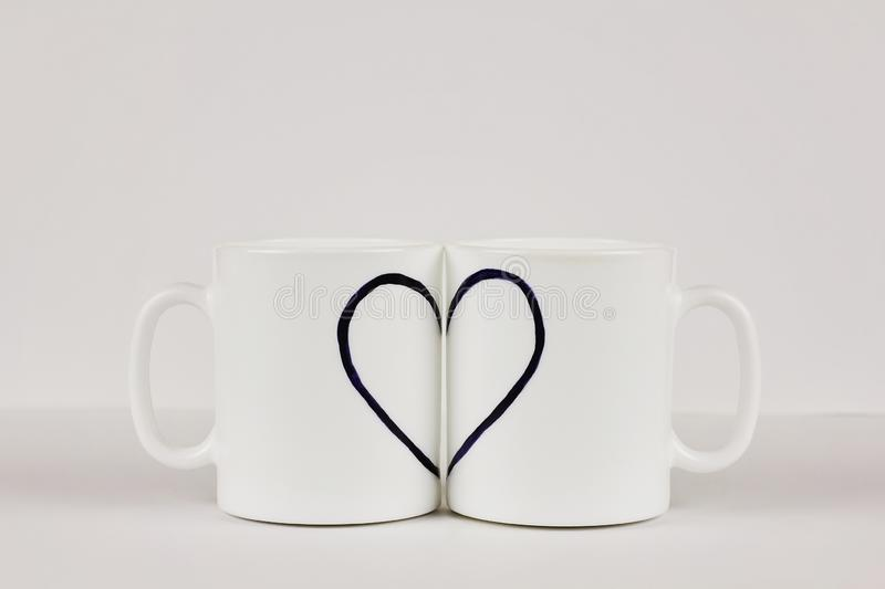 Drawn heart and two cups on white background. Valentine`s day, love, couple, wedding concept. Drawn heart and two white cups on white background with copy space stock photos