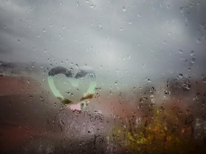 Drawn heart on the wet window pane with rain drops royalty free stock image