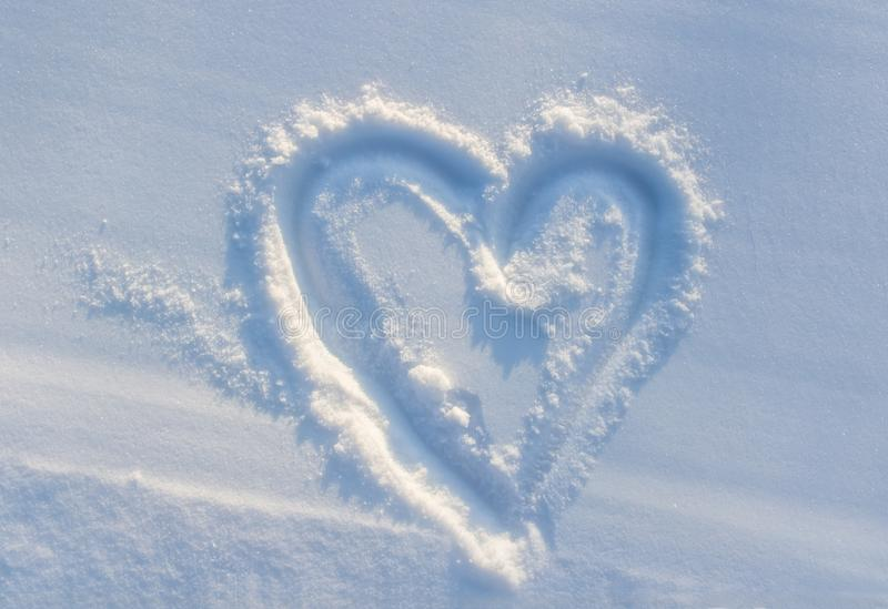 drawn heart on white snow. winter, frost stock images