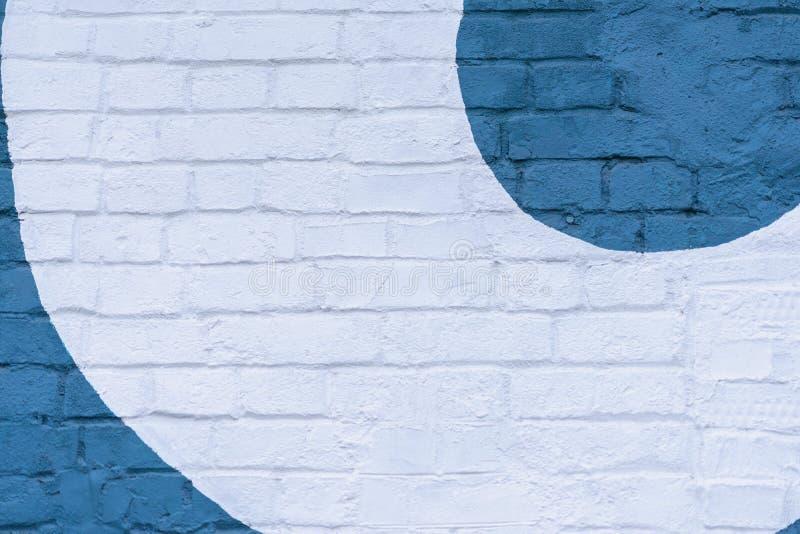Drawn painted blue several semicircles on light brick wall, stylish pattern, as graffiti. Graphic grunge texture. Drawn painted blue several semicircles on a stock photography