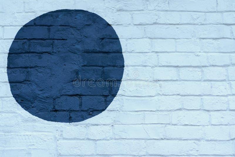 Drawn painted dark blue circle on light blue brick wall bricks surface of wall, as graffiti. Graphic grunge texture royalty free stock photos