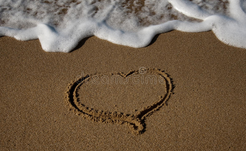 Drawn in the sand heart with the oncoming wave. Valentine's Day with your beloved on the beaches of Europe royalty free stock photos